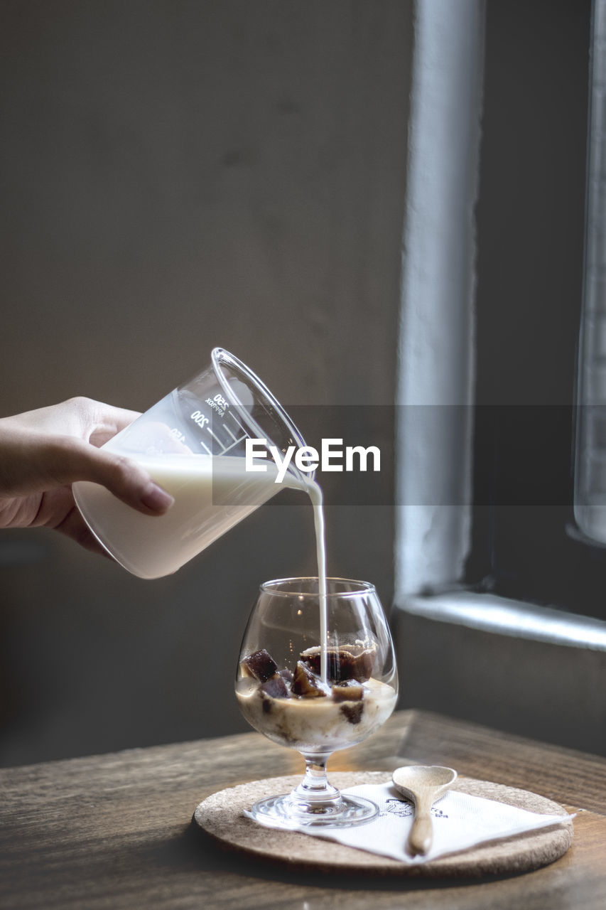 Cropped Hand Pouring Milk In Wineglass With Ice Cubes On Table