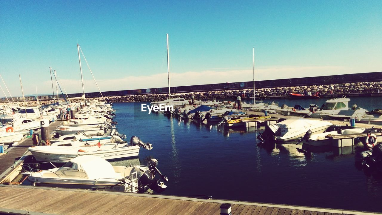 nautical vessel, water, moored, sea, transportation, boat, outdoors, mode of transport, harbor, clear sky, blue, sunlight, day, beach, nature, sailboat, large group of people, sky, yacht, mast, beauty in nature