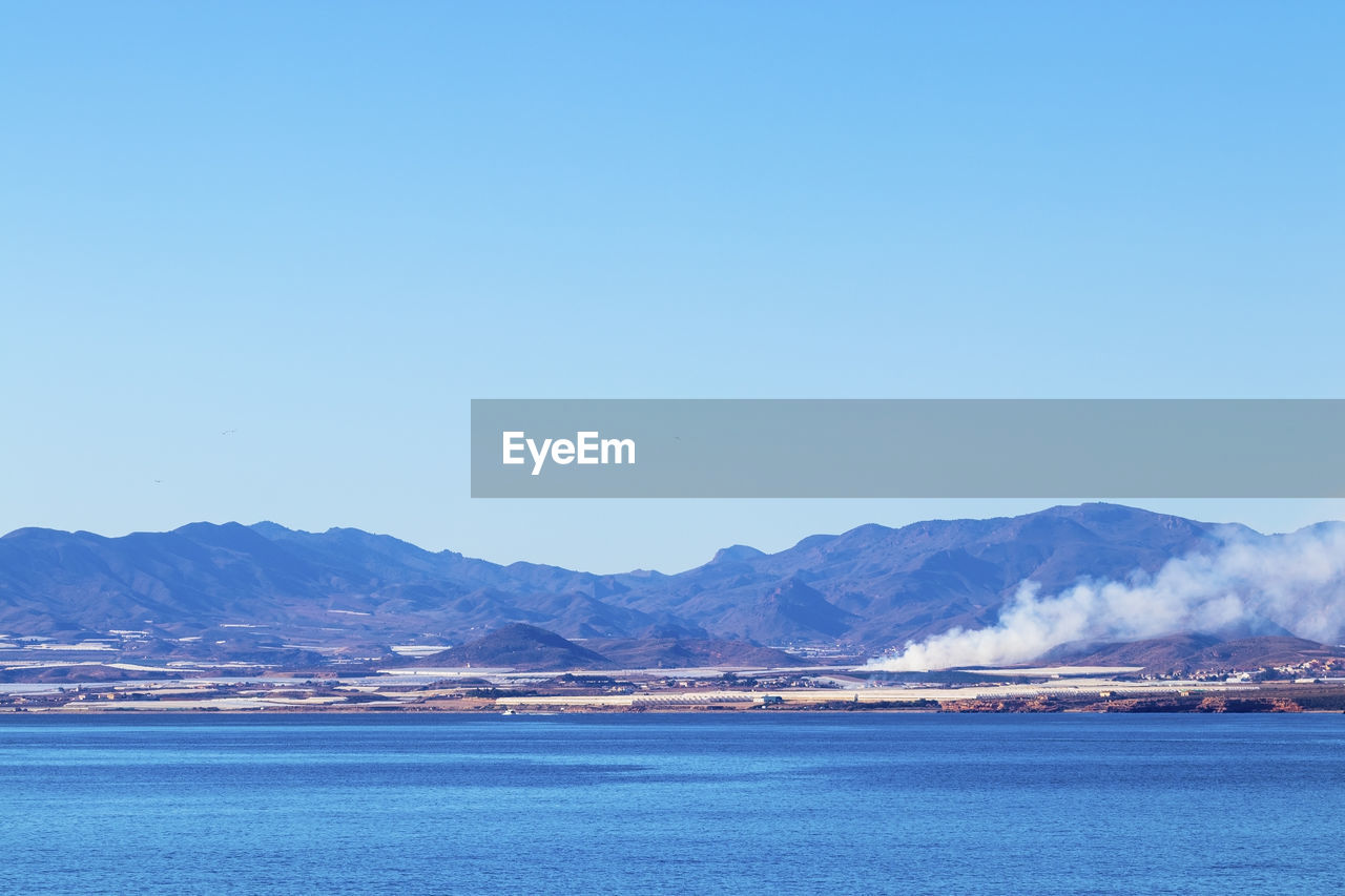 sky, mountain, blue, copy space, scenics - nature, beauty in nature, tranquil scene, water, clear sky, tranquility, nature, no people, waterfront, sea, mountain range, day, outdoors, travel, transportation, bay, view into land