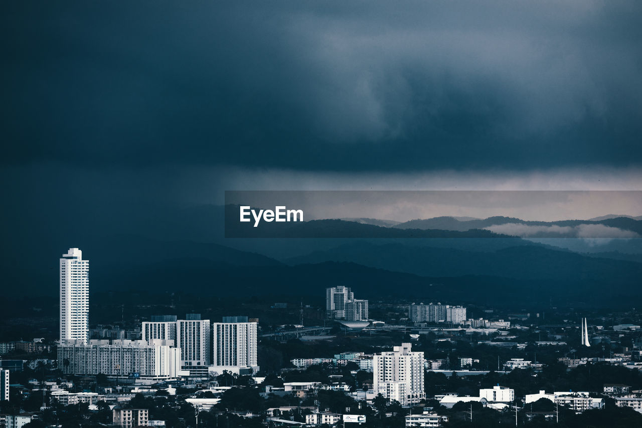 VIEW OF BUILDINGS IN CITY AGAINST STORM CLOUD