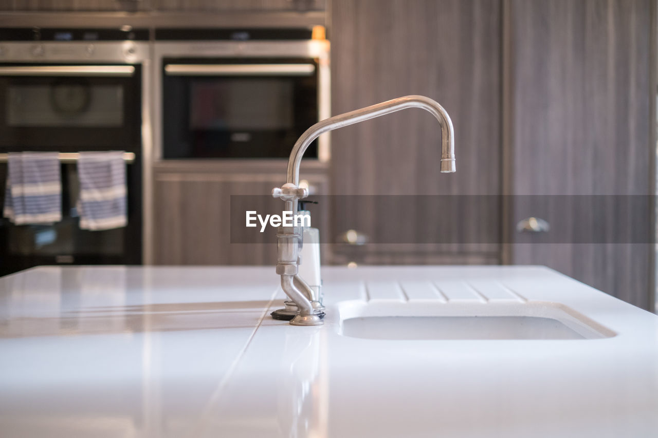 Kitchen sink against cabinet at home