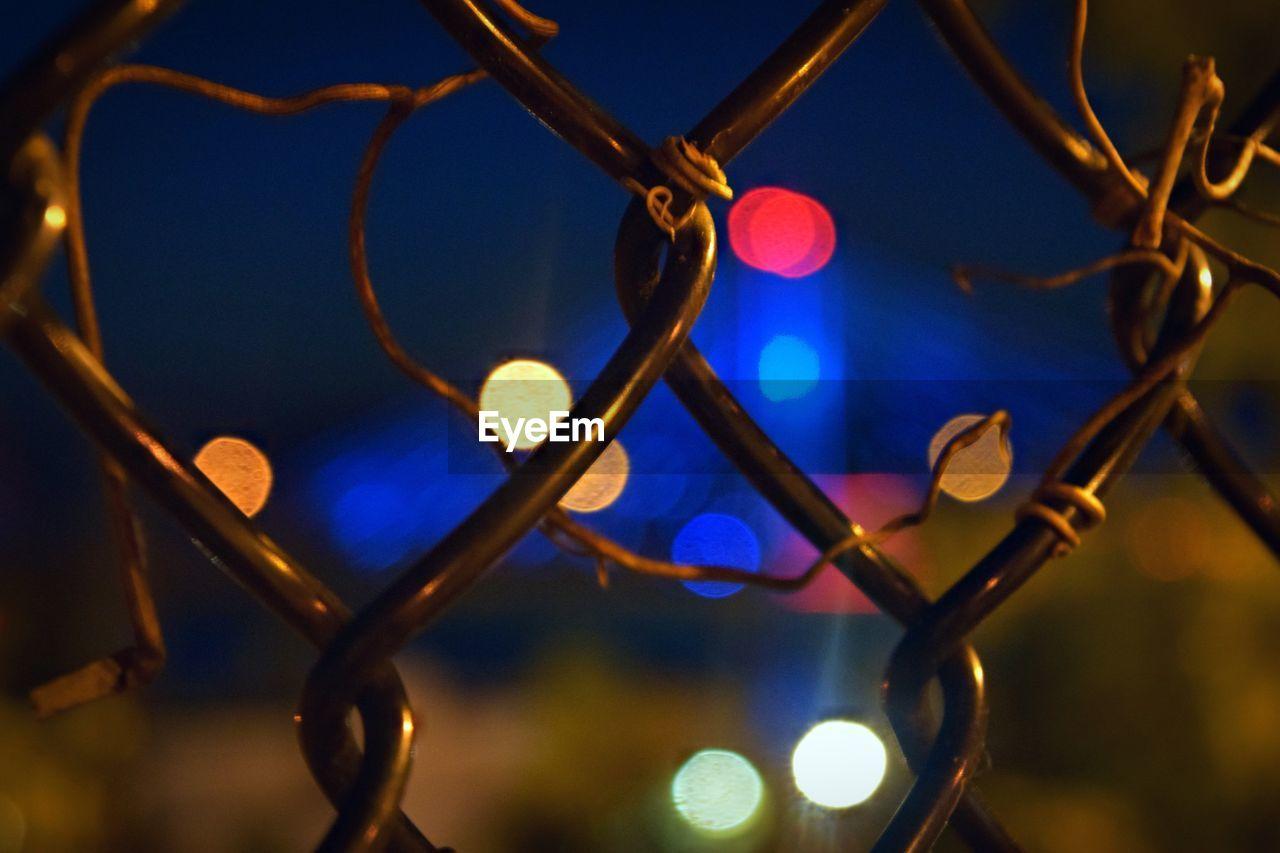 Close-up of illuminated defocused lights seen through fence at night