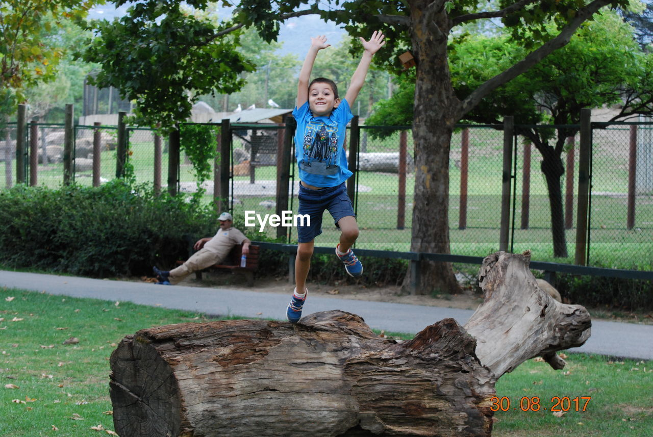 Adult Architecture Boys Casual Clothing Cheerful Child Childhood Children Only Day Full Length Fun Grass Happiness Jumping Looking At Camera One Boy Only One Person Outdoors People Playing Portrait Smiling Tree Tree Trunk