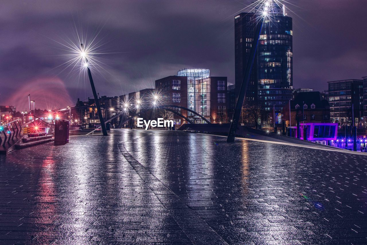 built structure, architecture, city, night, building exterior, illuminated, water, sky, transportation, building, nature, reflection, office building exterior, street, river, city life, tall - high, light beam, skyscraper, no people, cityscape, outdoors, modern, rain