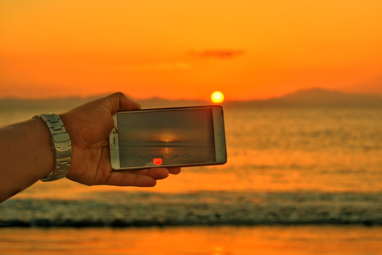 human hand, sunset, hand, human body part, one person, sky, holding, orange color, technology, real people, wireless technology, communication, sea, photography themes, water, smart phone, portable information device, lifestyles, nature, beauty in nature, sun, outdoors, finger