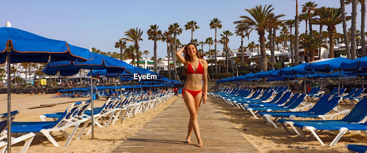 Portrait Of Woman In Bikini Standing At Beach