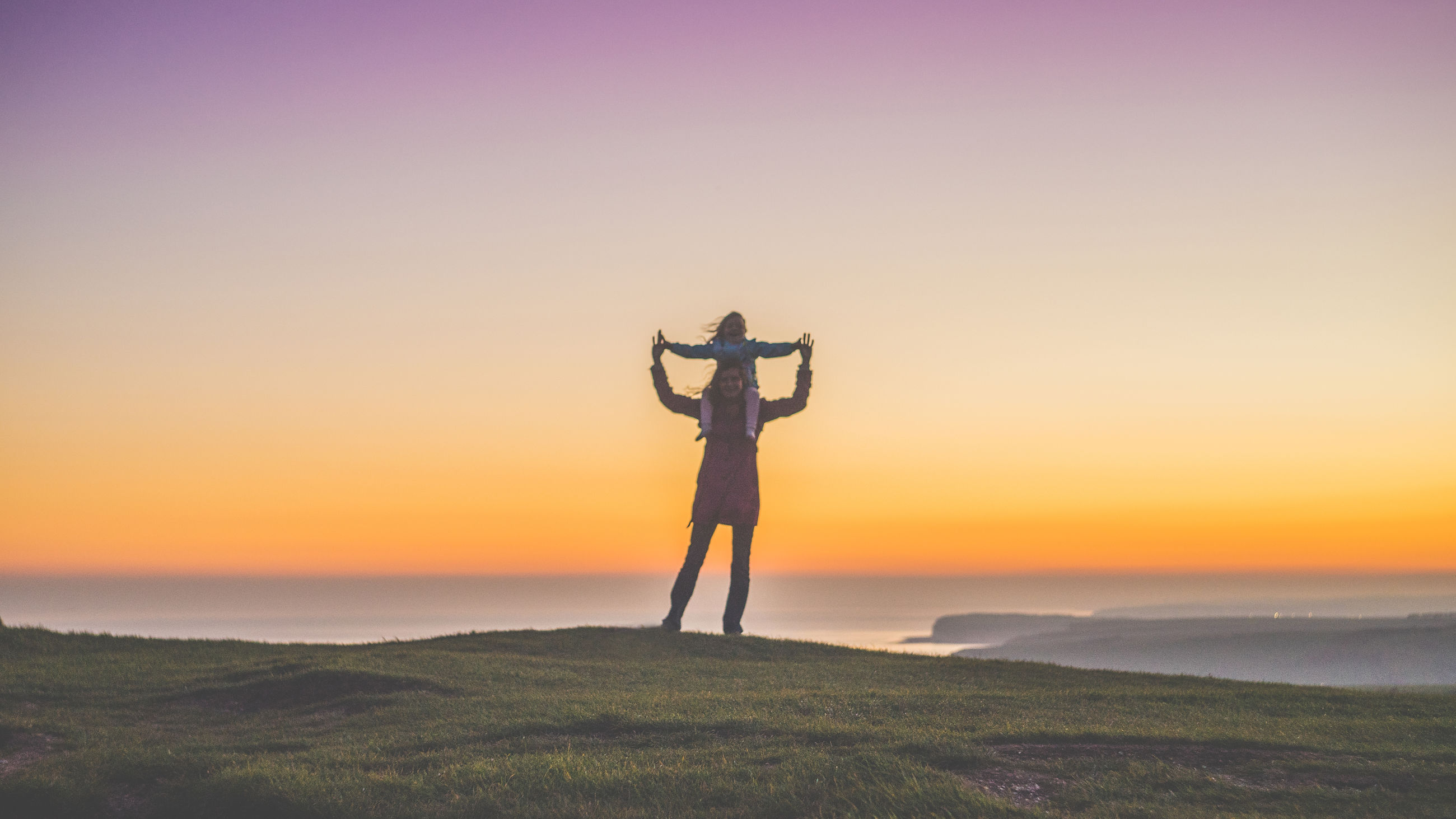 Woman piggybacking daughter while standing on field by sea against sky during sunset