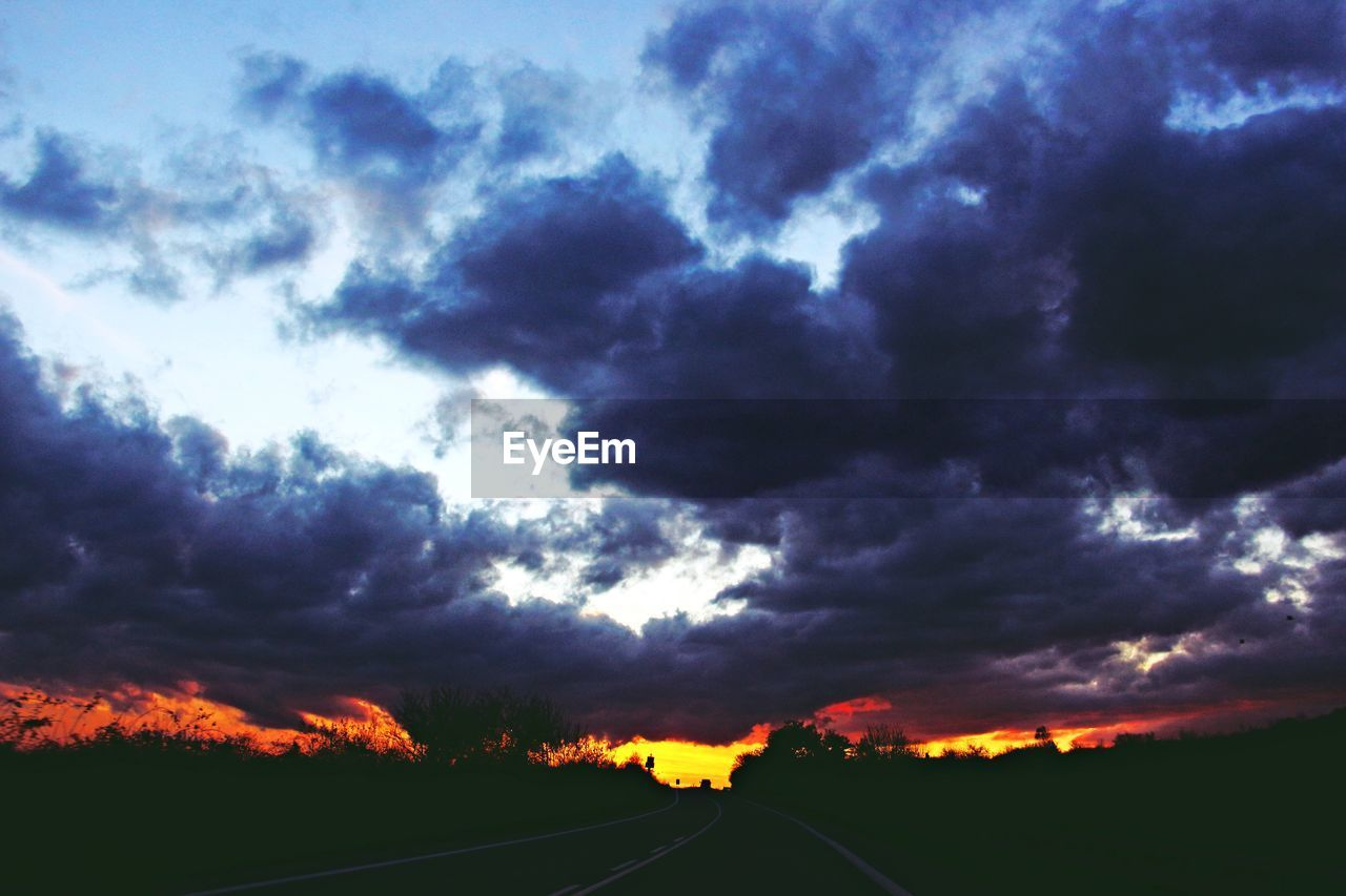 cloud - sky, road, sky, scenics, dramatic sky, transportation, atmospheric mood, nature, sunset, tranquility, no people, tranquil scene, landscape, beauty in nature, the way forward, storm cloud, silhouette, outdoors, day, blue, tree