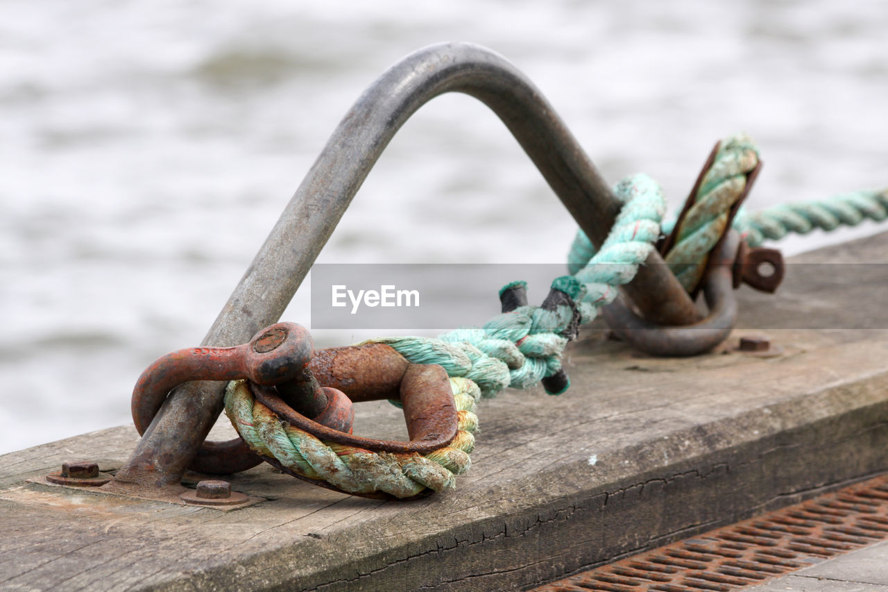 Close-up of rope tied to rusty metallic bollard on pier