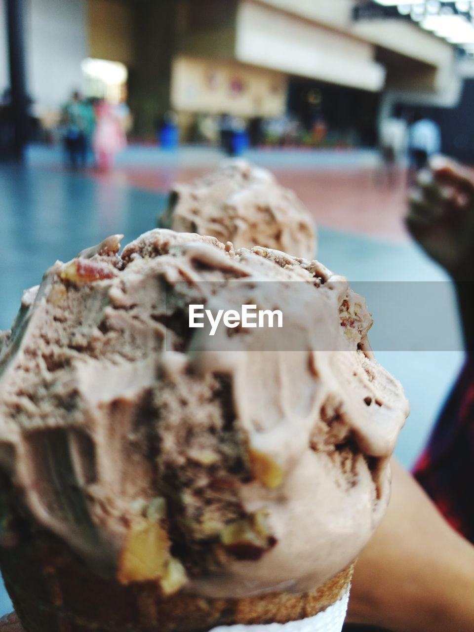 food and drink, one person, holding, real people, human hand, close-up, selective focus, photographing, focus on foreground, human body part, mobile phone, photography themes, wireless technology, food, freshness, day, indoors, photo messaging, ice cream, ready-to-eat, people