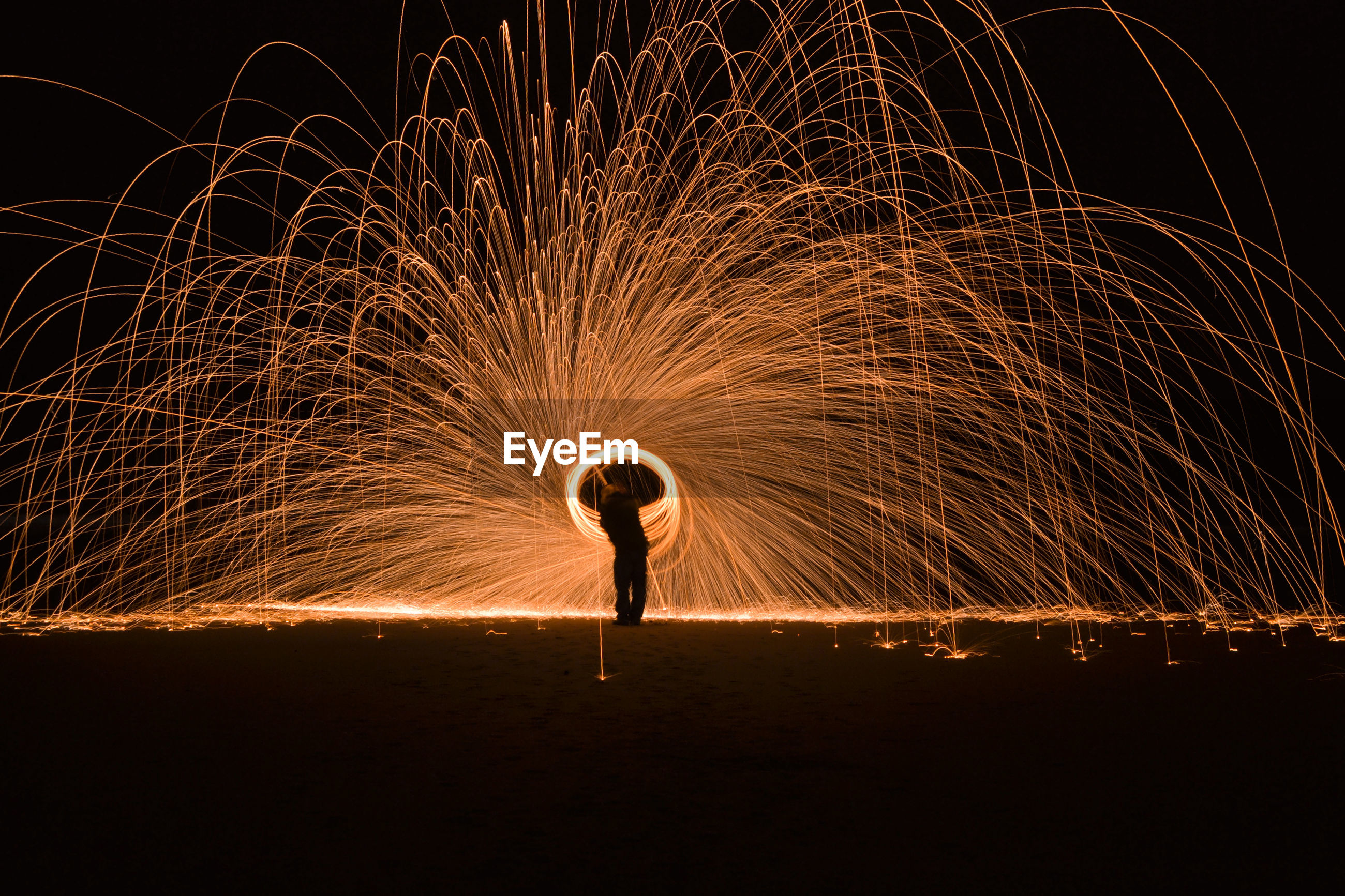 Full length of silhouette man spinning wire wool at night