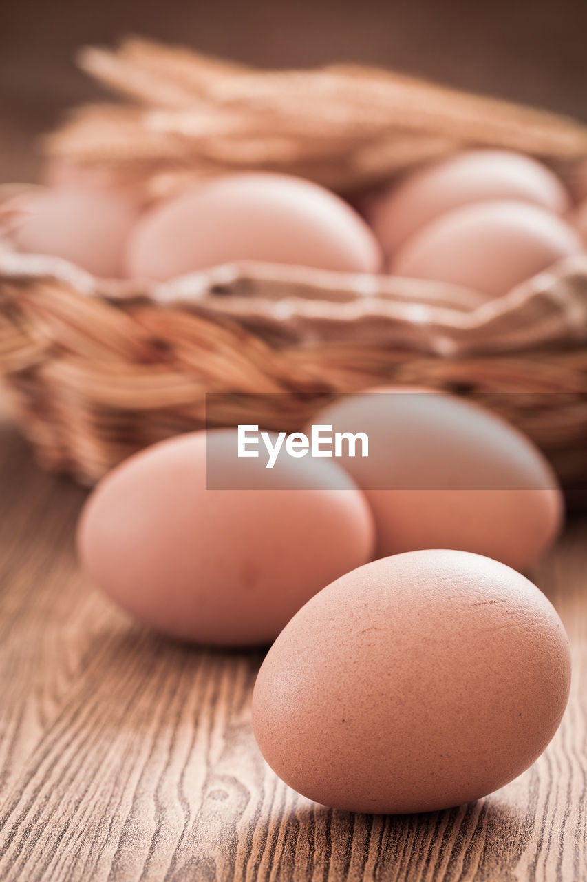 food, egg, food and drink, freshness, wellbeing, table, healthy eating, still life, brown, no people, close-up, raw food, indoors, focus on foreground, selective focus, wood - material, fragility, vulnerability, animal egg, container