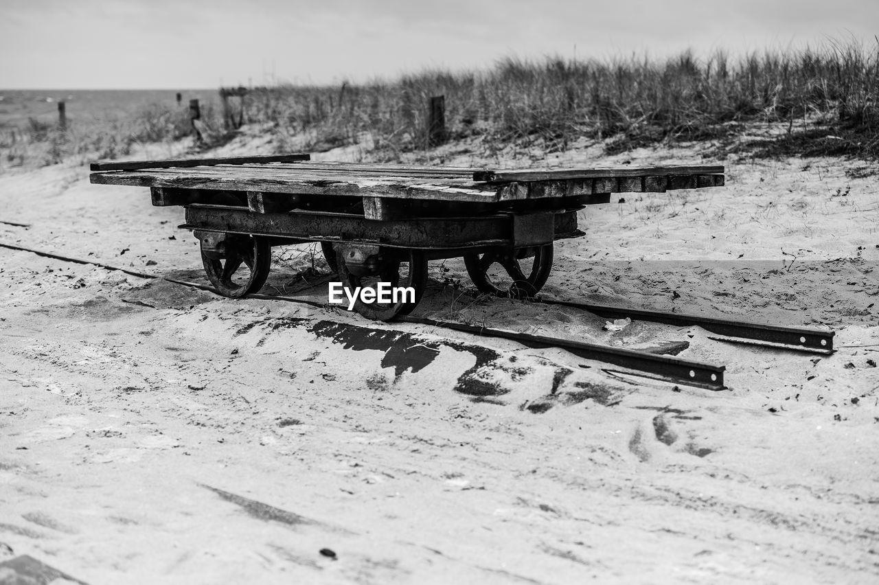 Abandoned Trailer On Railroad Track At Beach Against Sky
