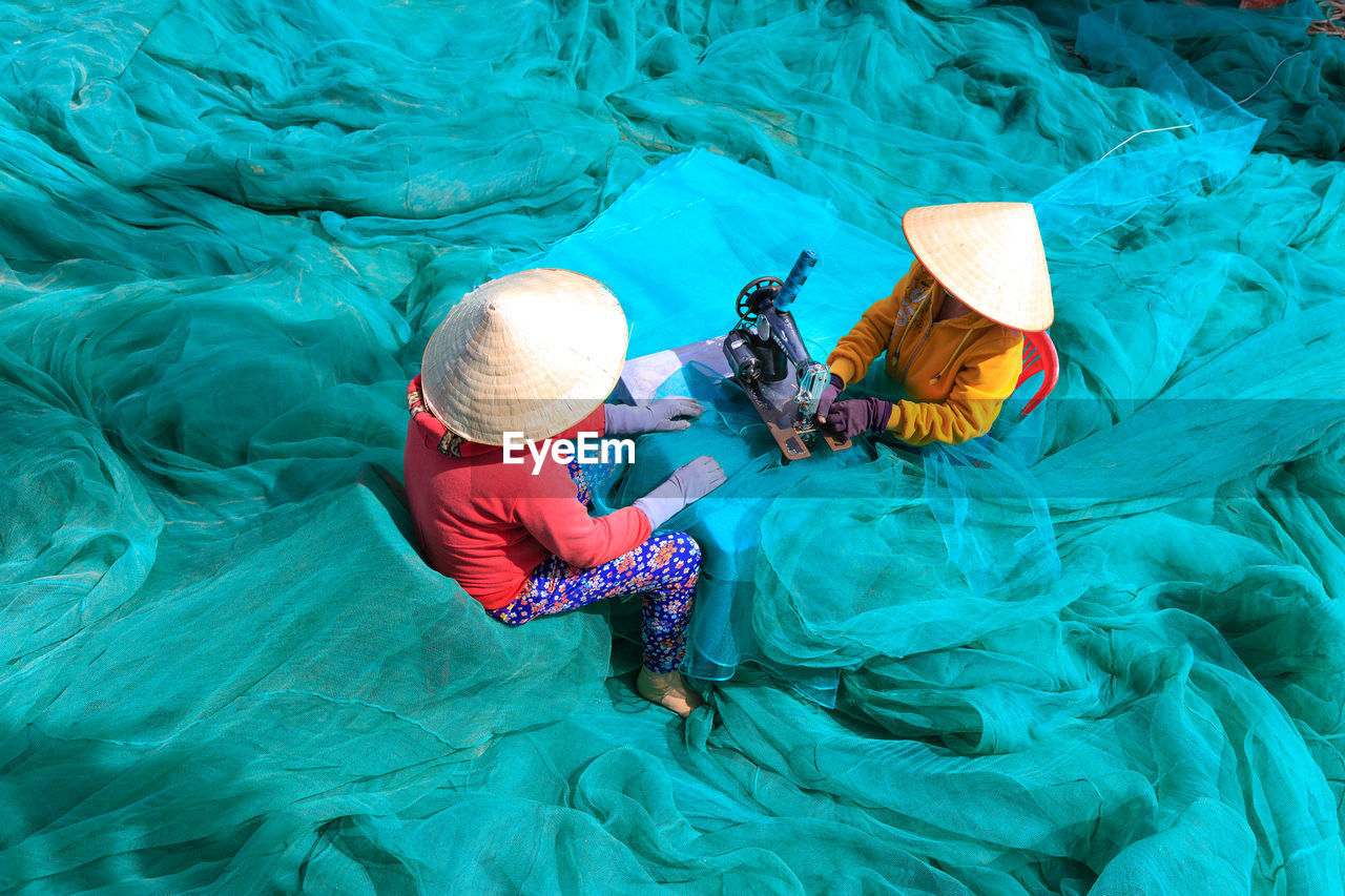 High Angle View Of Women Sewing Net