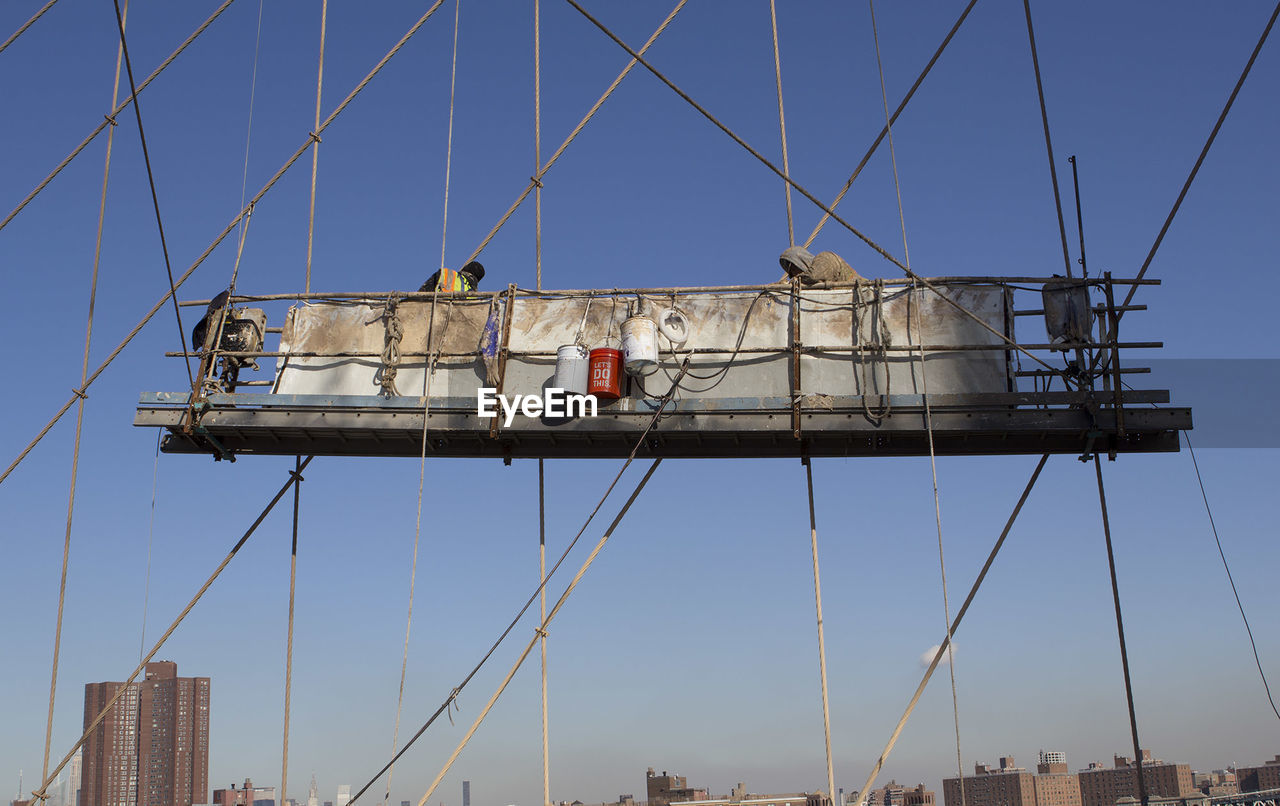 Low Angle View Of Workers Amidst Bridge Steel Cables Against Clear Blue Sky