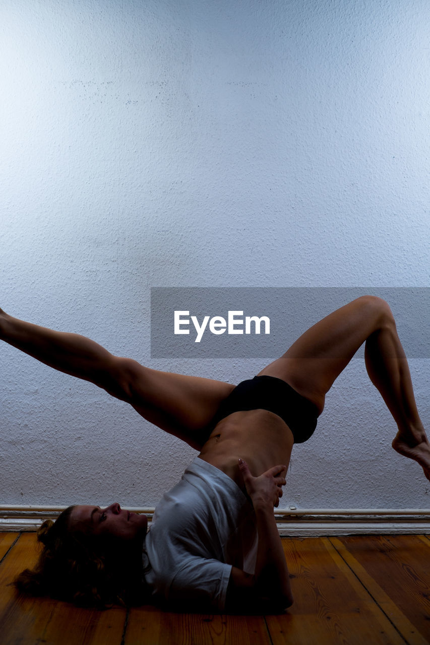 Side view of woman practicing shoulder stand against white wall