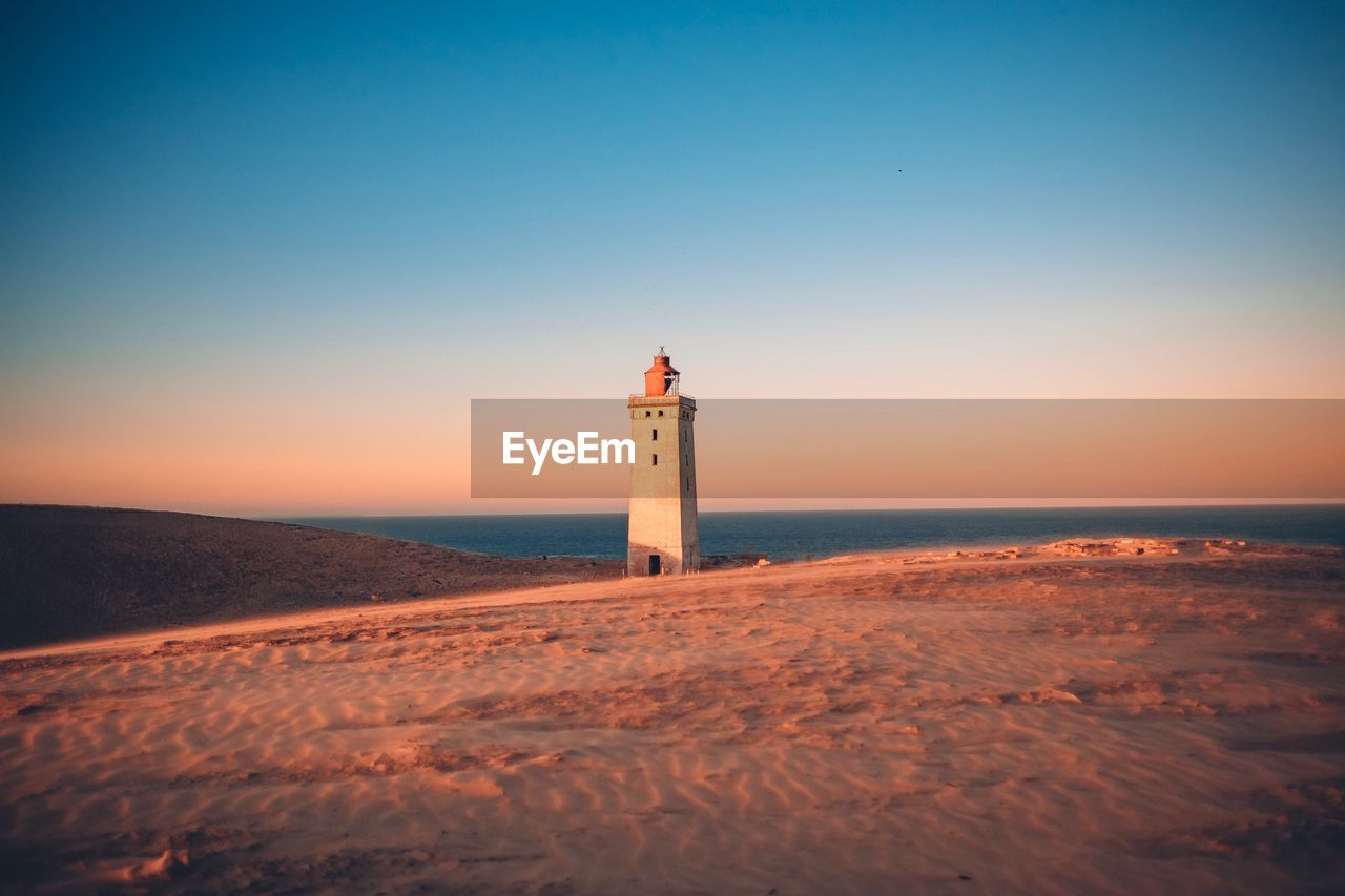 sea, sky, lighthouse, beach, water, tower, built structure, guidance, land, protection, building, safety, security, architecture, scenics - nature, direction, building exterior, horizon, horizon over water, clear sky, no people, outdoors