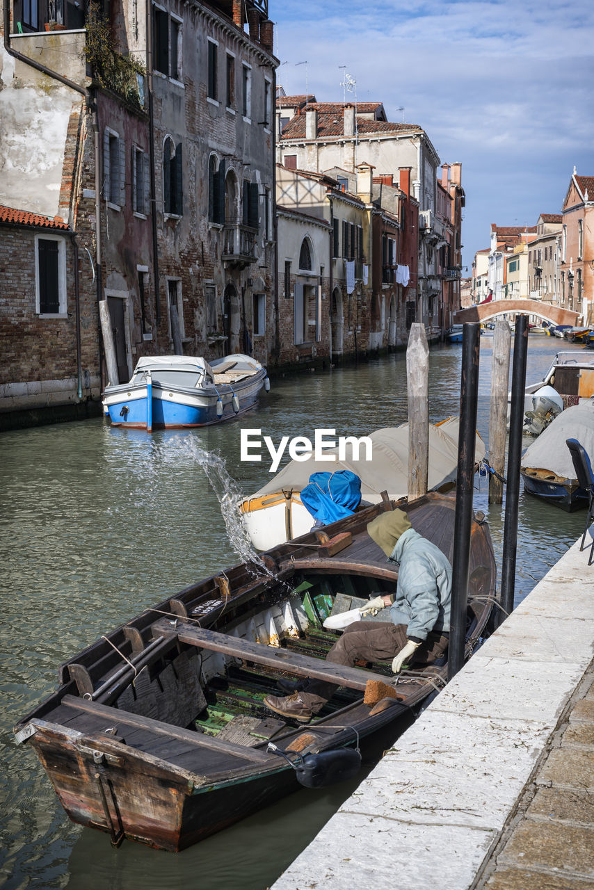 BOATS MOORED ON CANAL BY BUILDINGS IN CITY