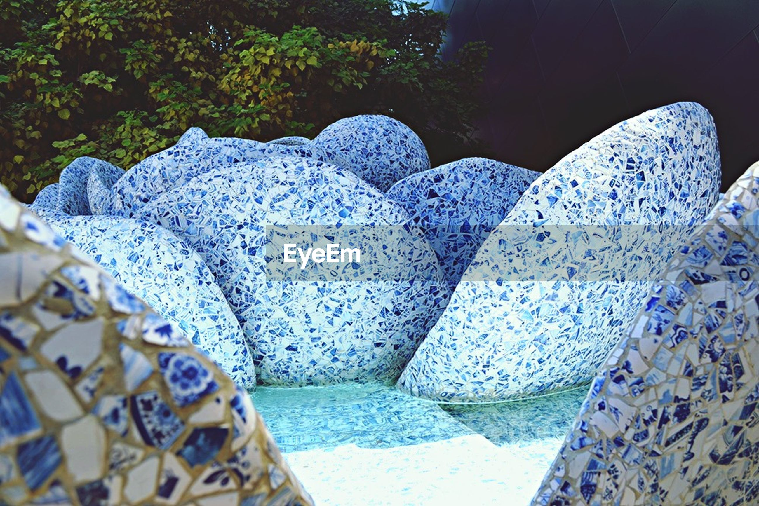 pattern, sunlight, blue, high angle view, day, built structure, stone material, outdoors, design, close-up, no people, architecture, textured, wall - building feature, shadow, nature, stone - object, water, in a row, rock - object