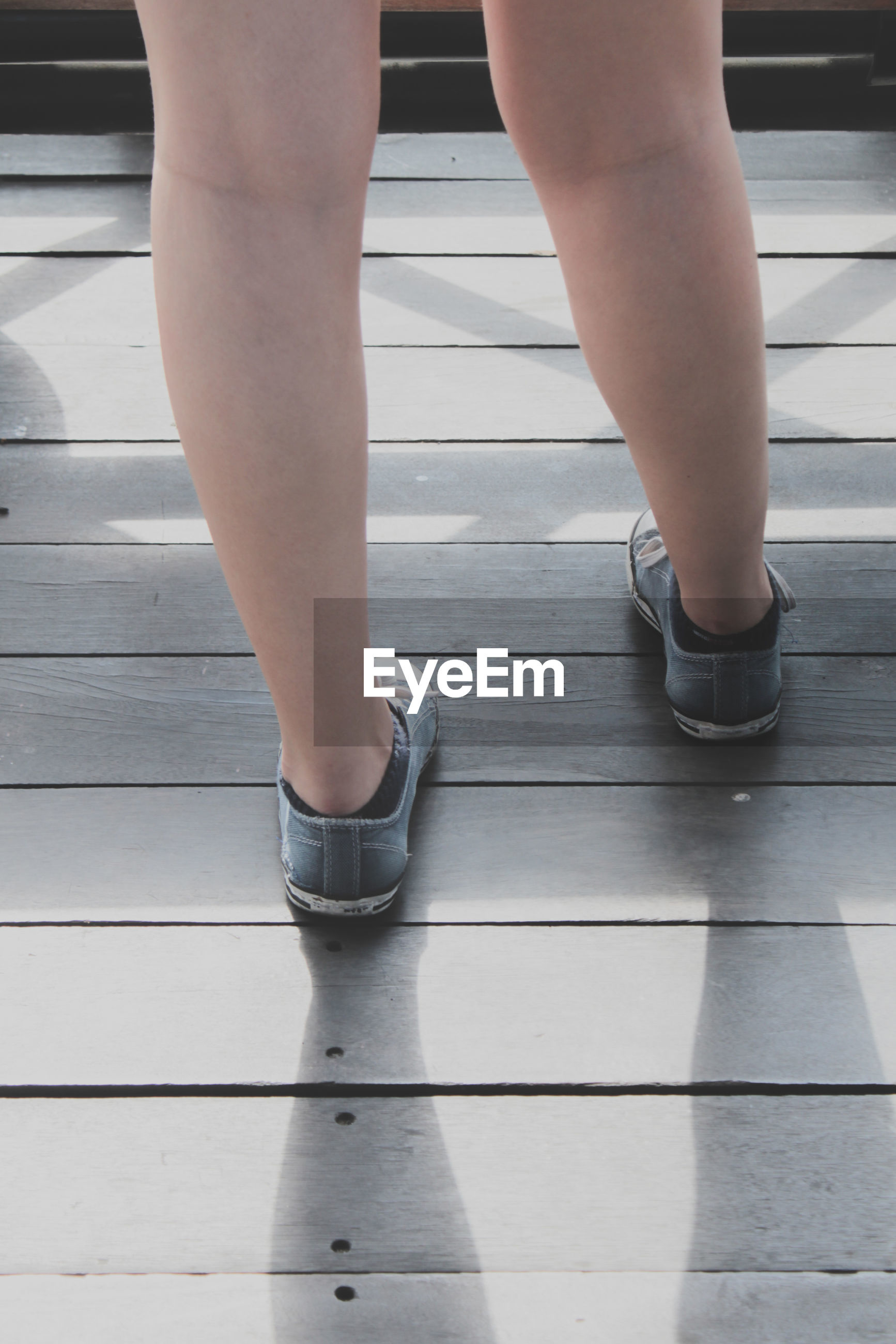 Low section of woman standing on deck