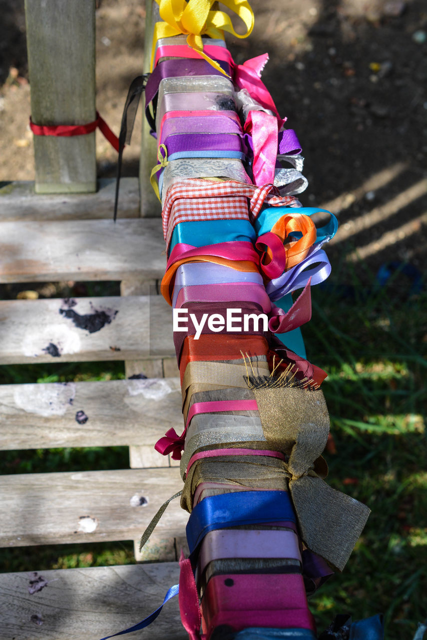High angle view of colorful fabrics tied on railing
