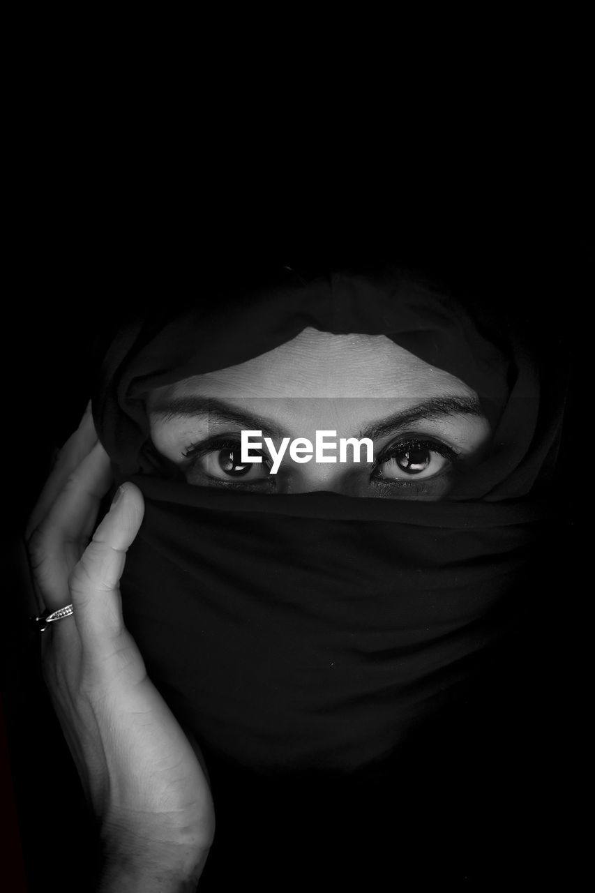 Portrait of woman with covered face against black background
