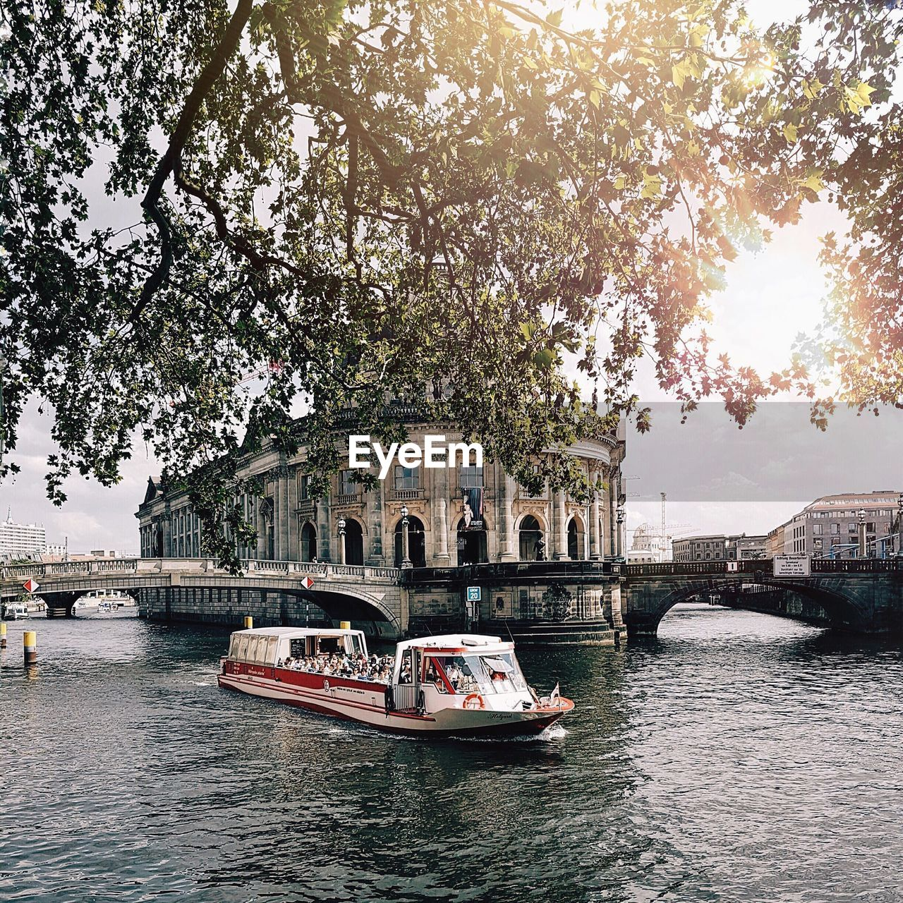 nautical vessel, transportation, tree, built structure, architecture, mode of transport, water, day, building exterior, river, outdoors, waterfront, bridge - man made structure, nature, large group of people, travel destinations, sky, city, people