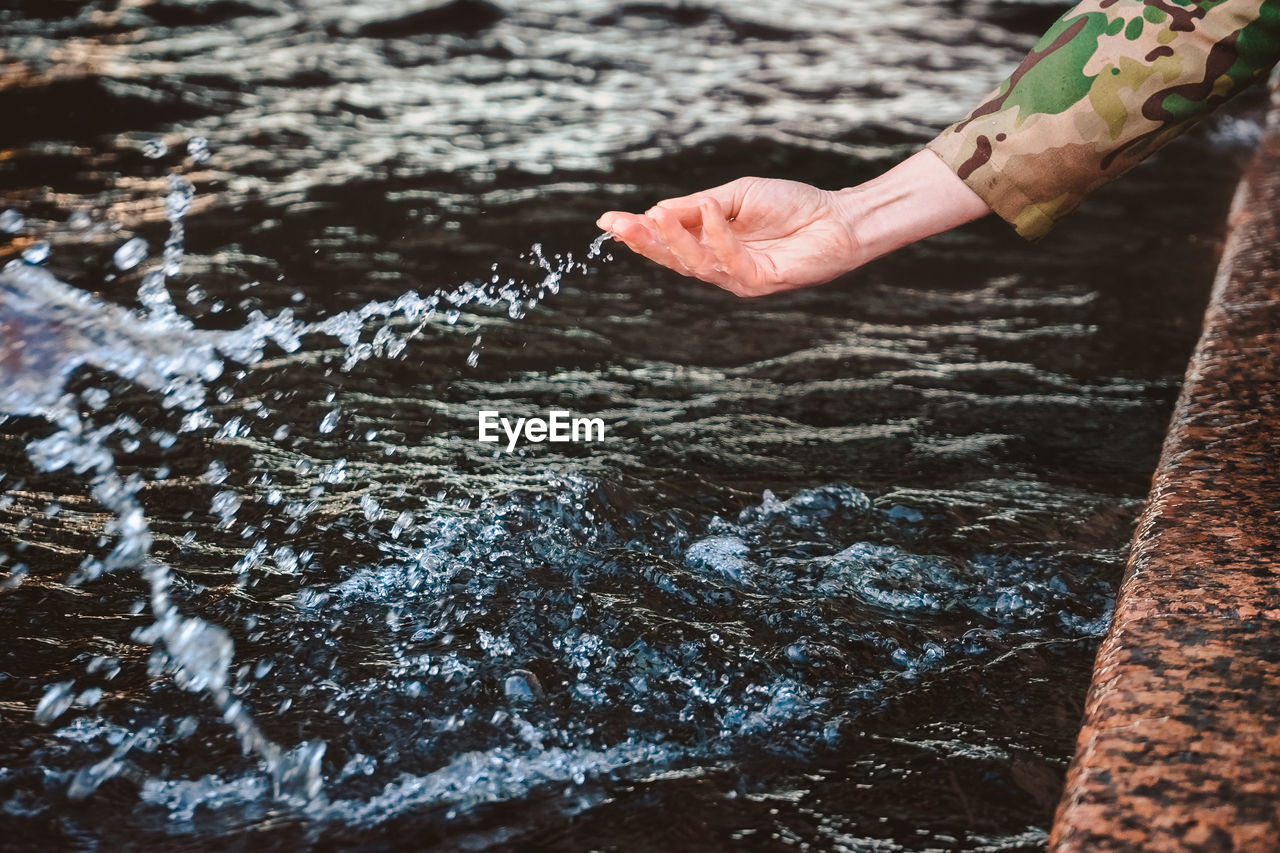 The girl's hand splashes water and drops fly. touching the river with the palm of your hand