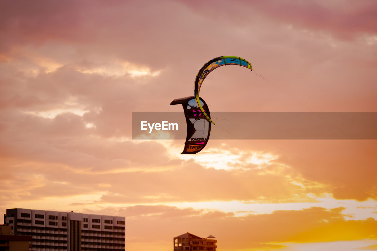 sunset, sky, cloud - sky, adventure, extreme sports, leisure activity, parachute, exhilaration, real people, nature, mid-air, sport, scenics, outdoors, beauty in nature, low angle view, paragliding, one person, lifestyles, flying, day, people