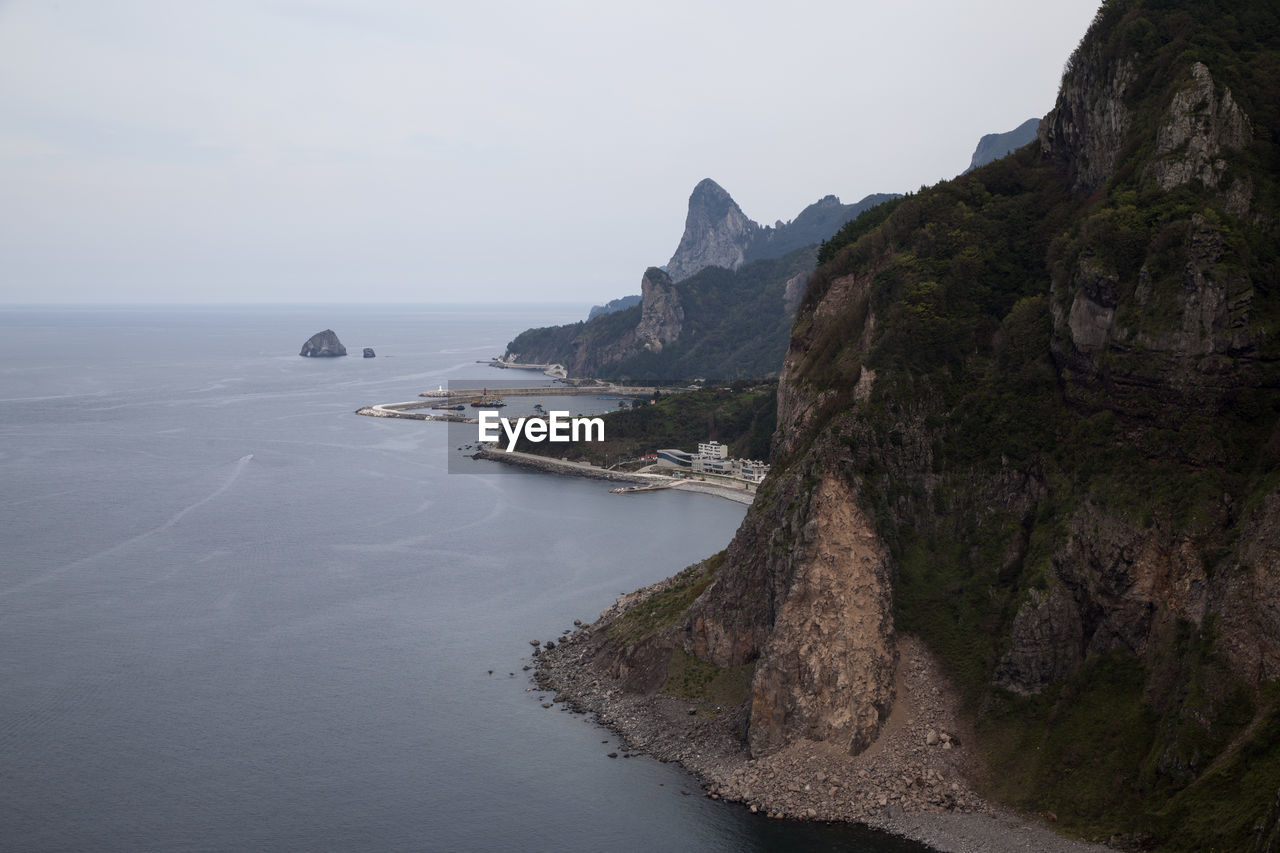 High Angle View Of Mountain By Sea Against Clear Sky