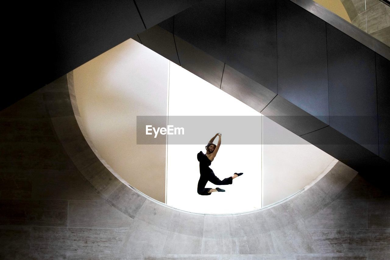 Low angle view of woman jumping against wall