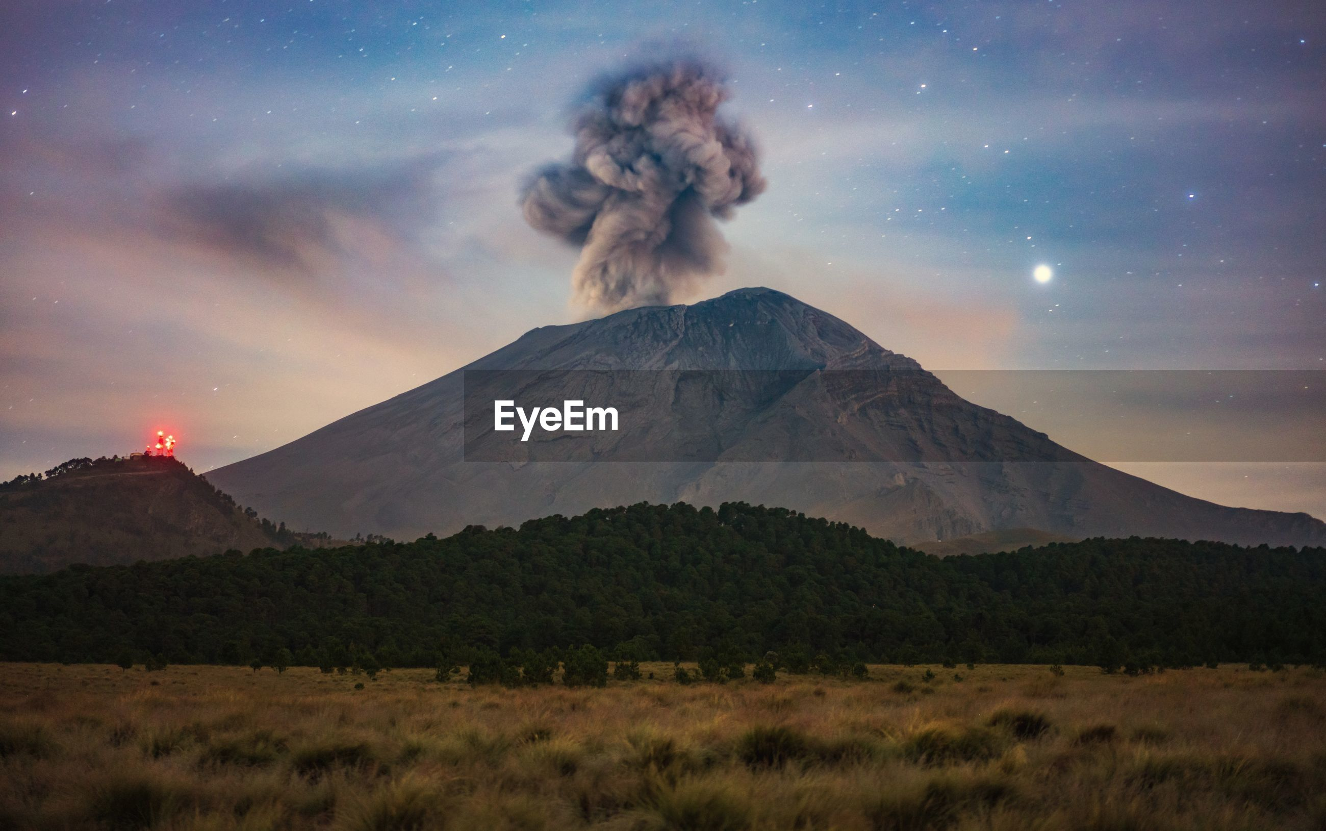 Scenic view of erupting volcanic mountain against sky during sunset