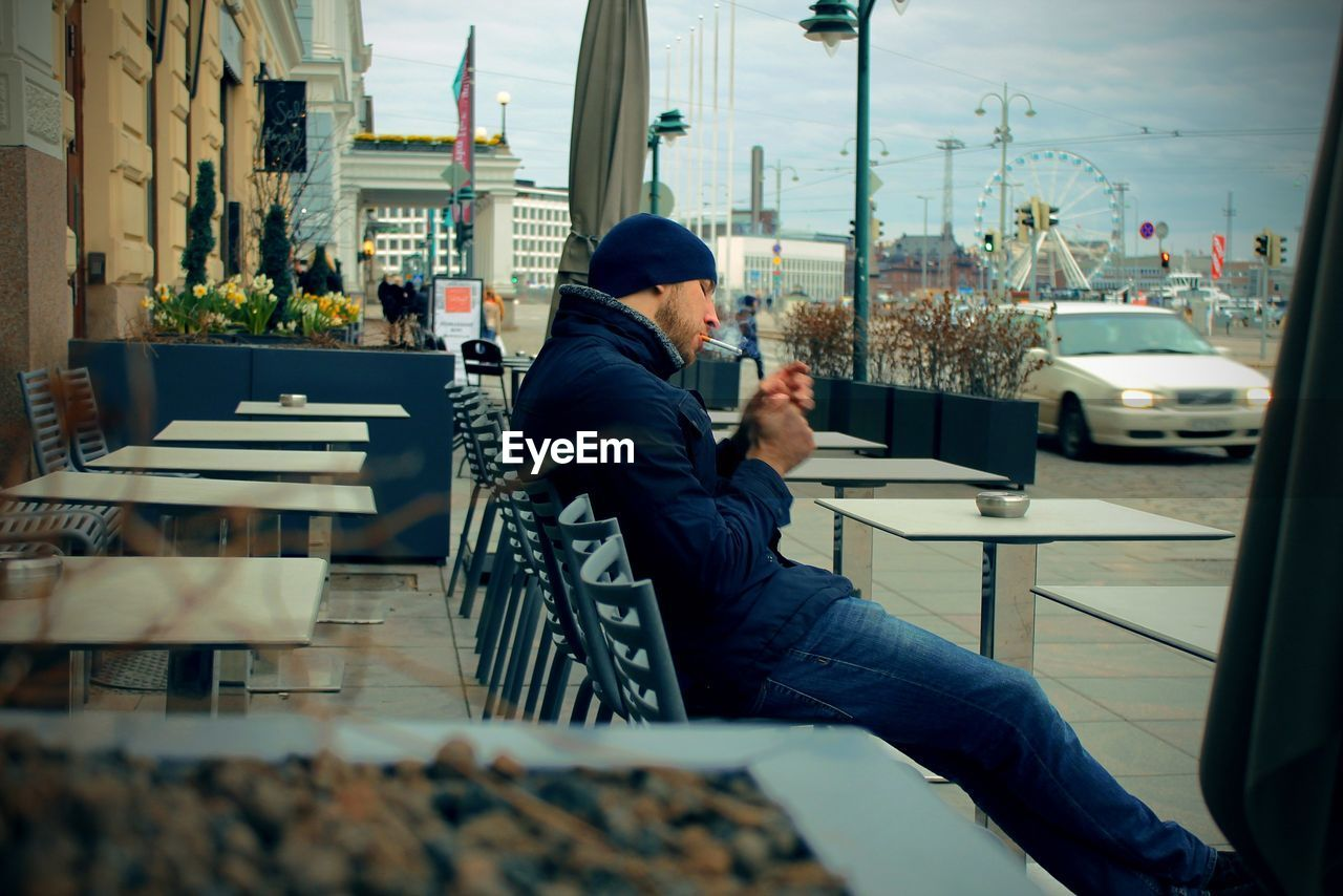 Man Smoking Cigarette While Sitting On Chair At Sidewalk Cafe In City