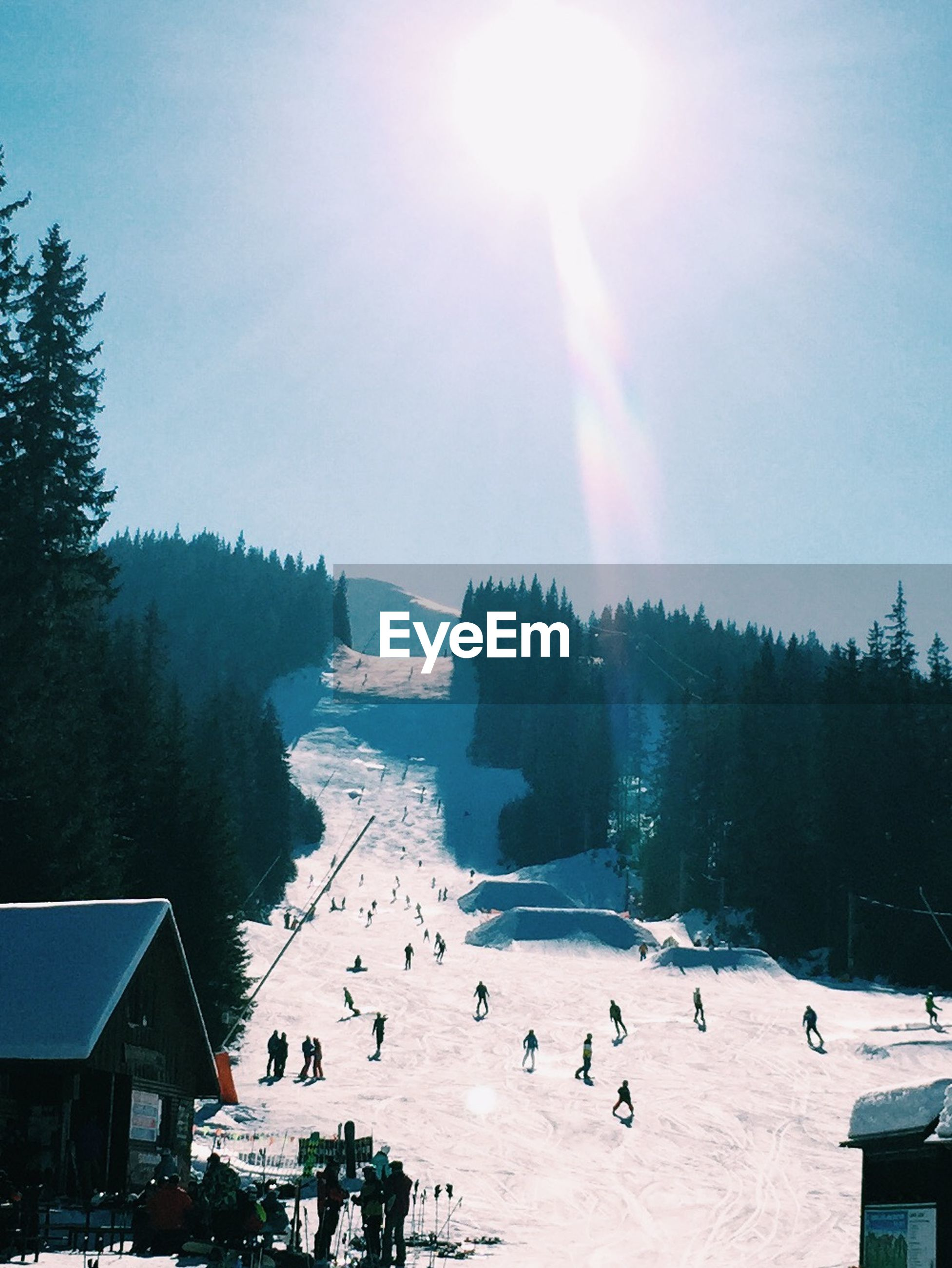 People skiing on snowy hill against sky on sunny day