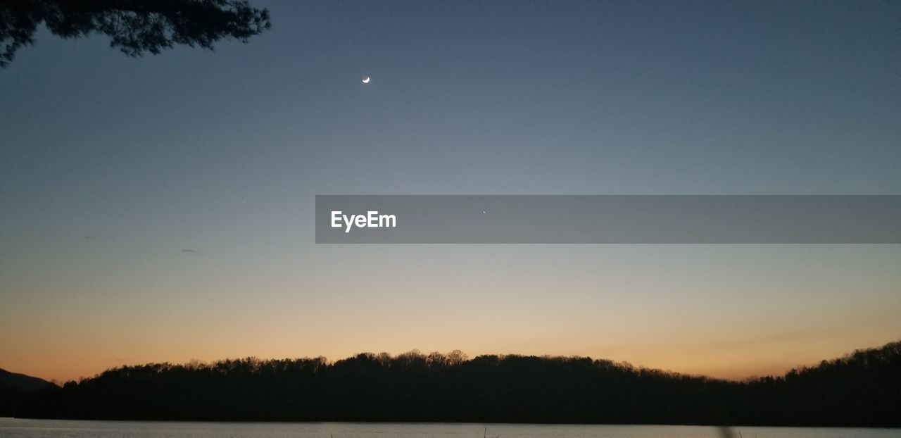 sky, moon, tranquility, beauty in nature, scenics - nature, tranquil scene, silhouette, tree, sunset, idyllic, nature, plant, crescent, no people, night, clear sky, copy space, space, non-urban scene, astronomy, outdoors, full moon, moonlight, planetary moon