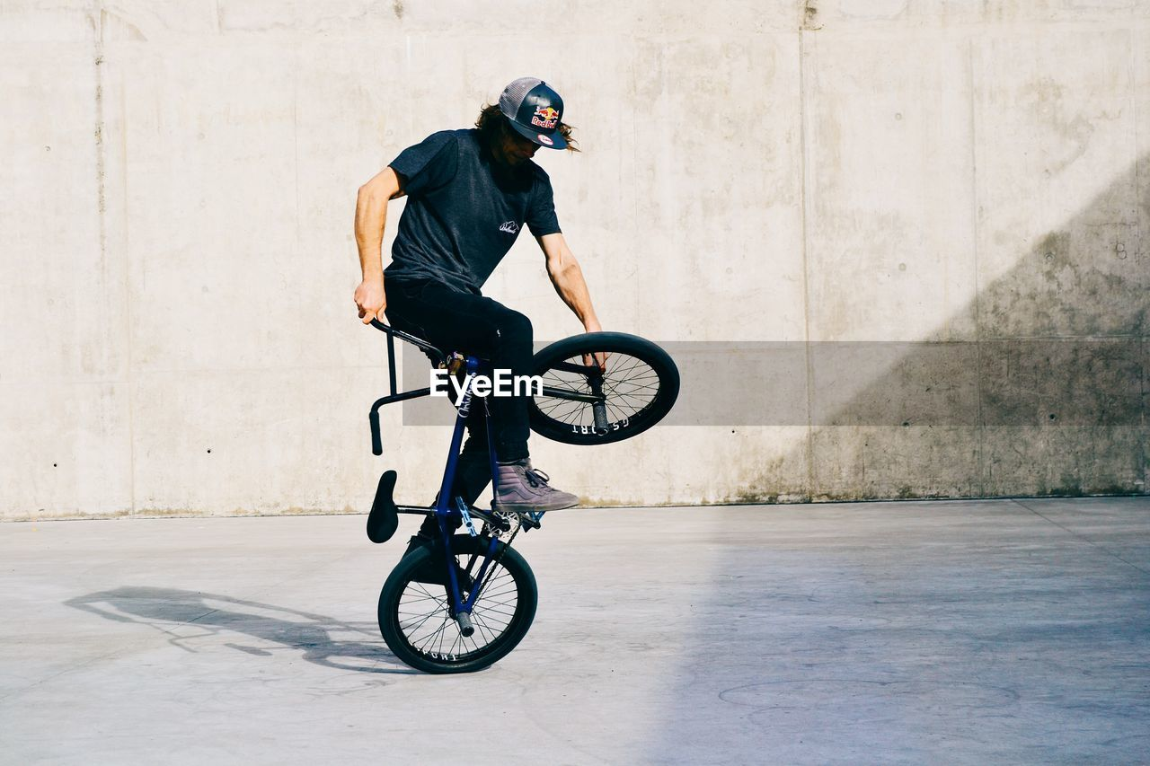 FULL LENGTH OF MAN RIDING BICYCLE ON SKATEBOARD