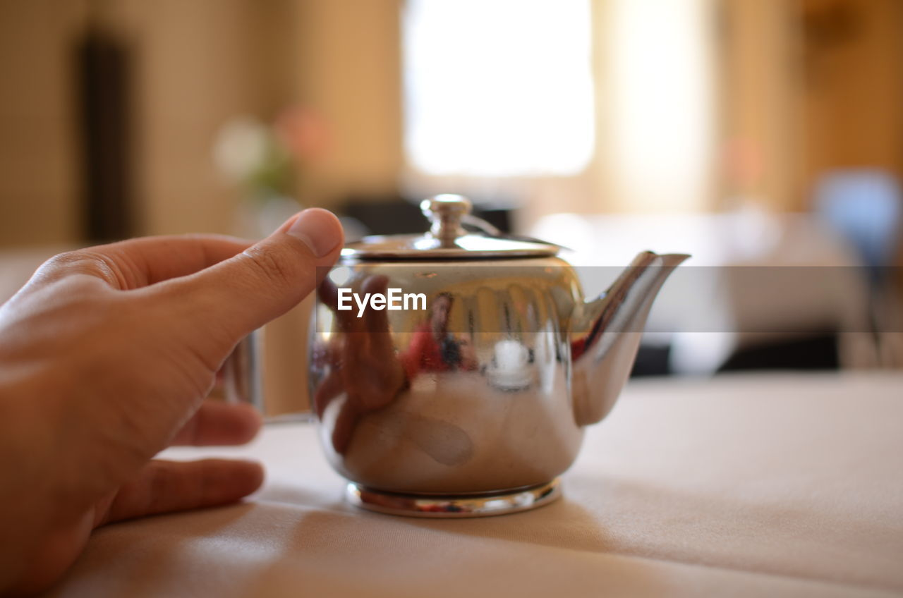 Close-Up Of Cropped Hand Holding Tea Kettle On Table
