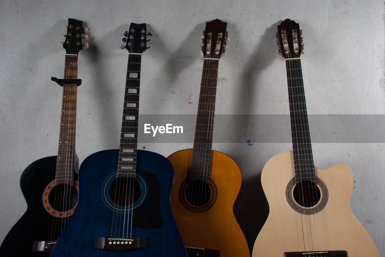 string instrument, music, guitar, musical instrument, musical equipment, acoustic guitar, arts culture and entertainment, indoors, string, wall - building feature, no people, musical instrument string, side by side, still life, wood - material, choice, variation, wind instrument, fretboard, close-up