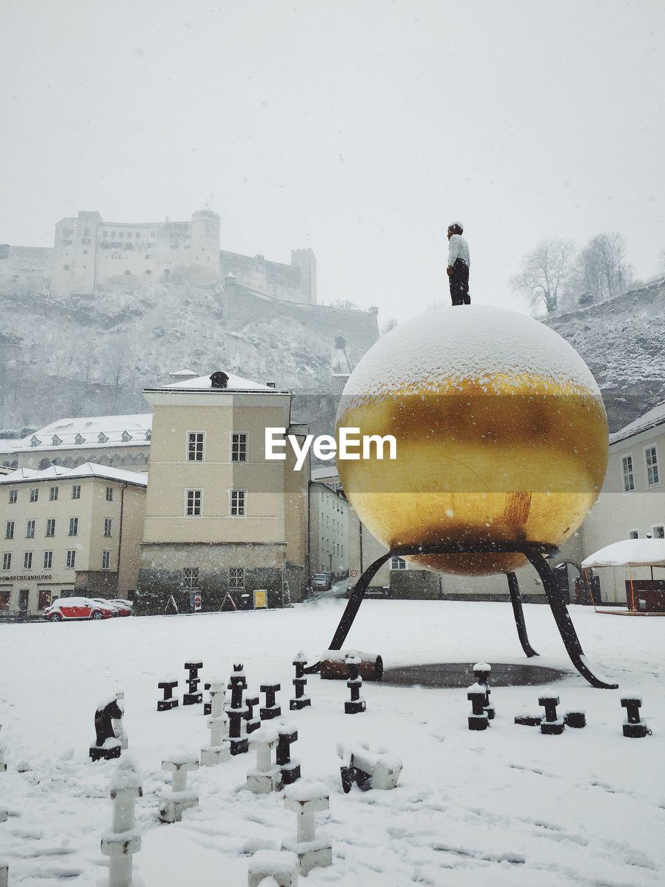 Sculpture of man on gilded sphere outside hohensalzburg castle