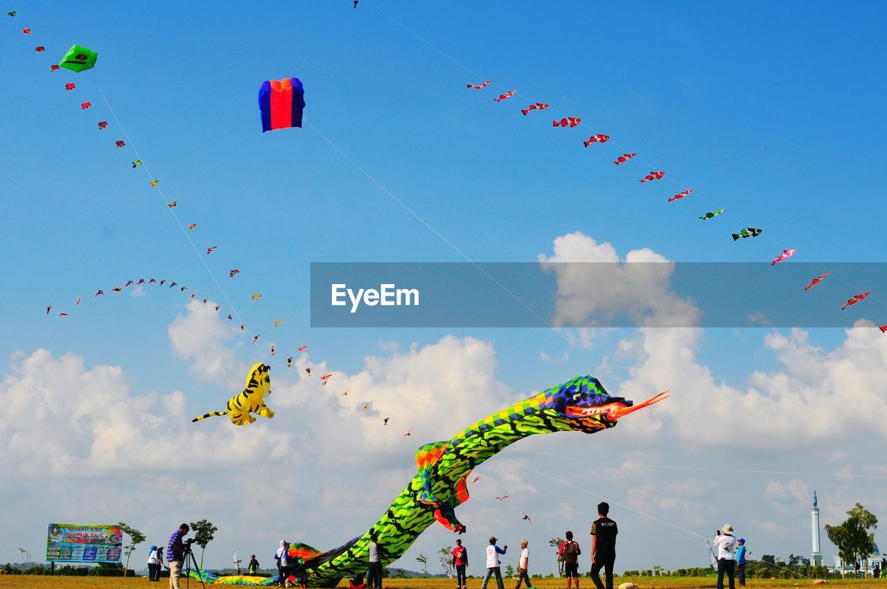 sky, cloud - sky, flying, multi colored, nature, decoration, celebration, day, low angle view, creativity, hanging, kite - toy, art and craft, representation, outdoors, traditional festival, festival, real people