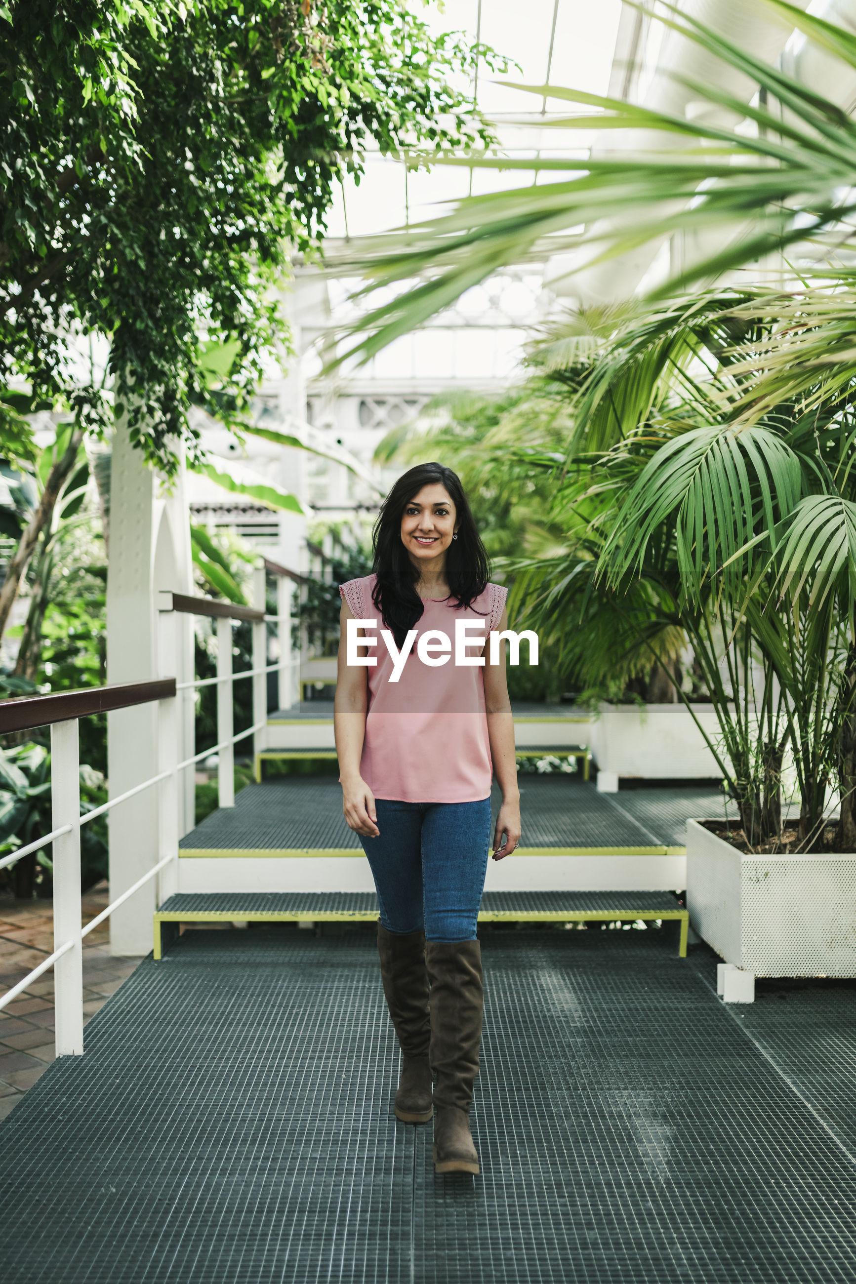 FULL LENGTH PORTRAIT OF WOMAN STANDING AGAINST PLANTS