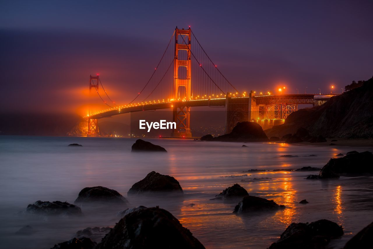 water, connection, sky, bridge, built structure, bridge - man made structure, suspension bridge, sunset, transportation, nature, architecture, sea, travel destinations, illuminated, bay of water, beauty in nature, no people, bay, outdoors