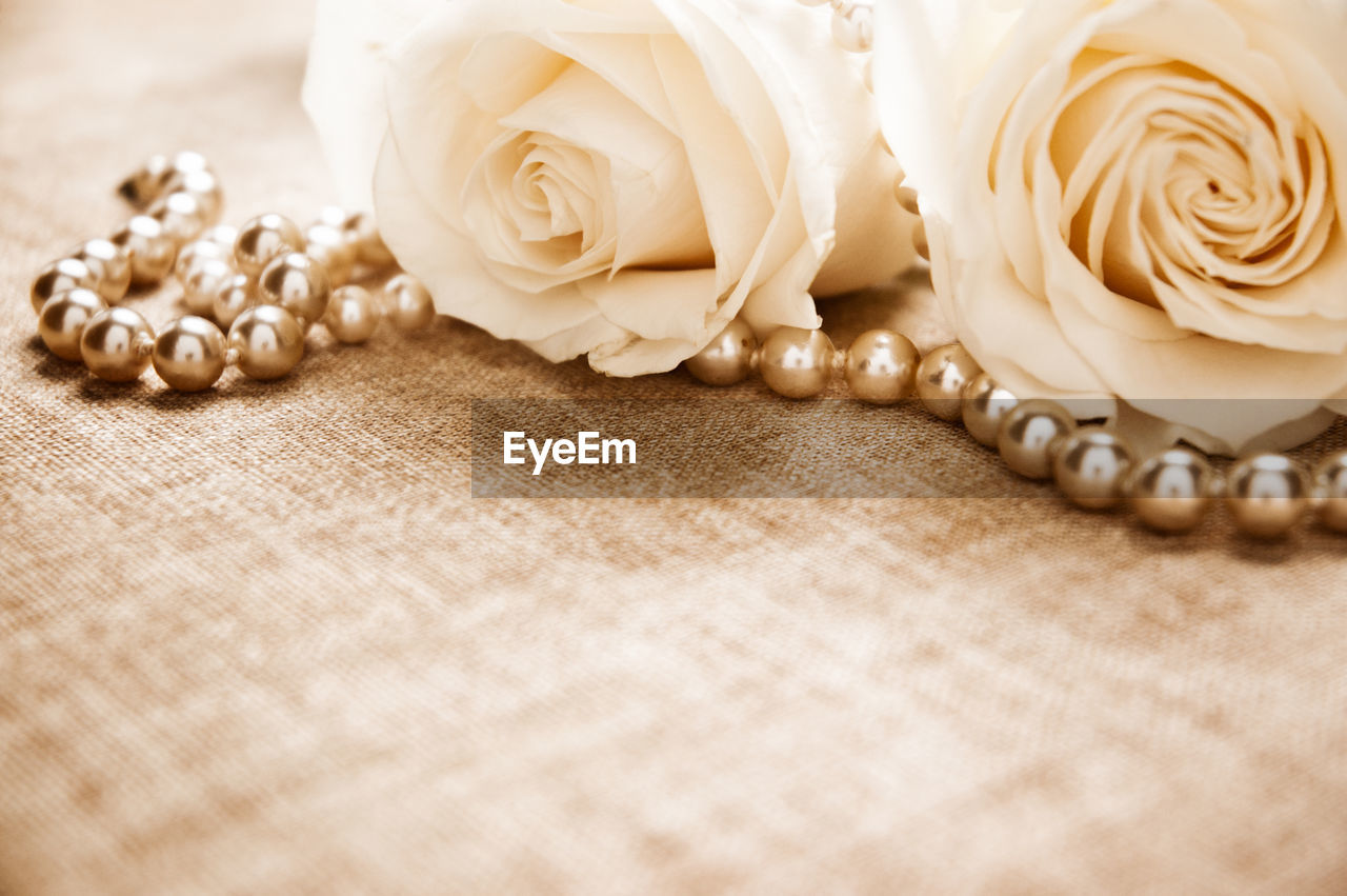 Close-Up Of Pearl Necklace With Roses On Table