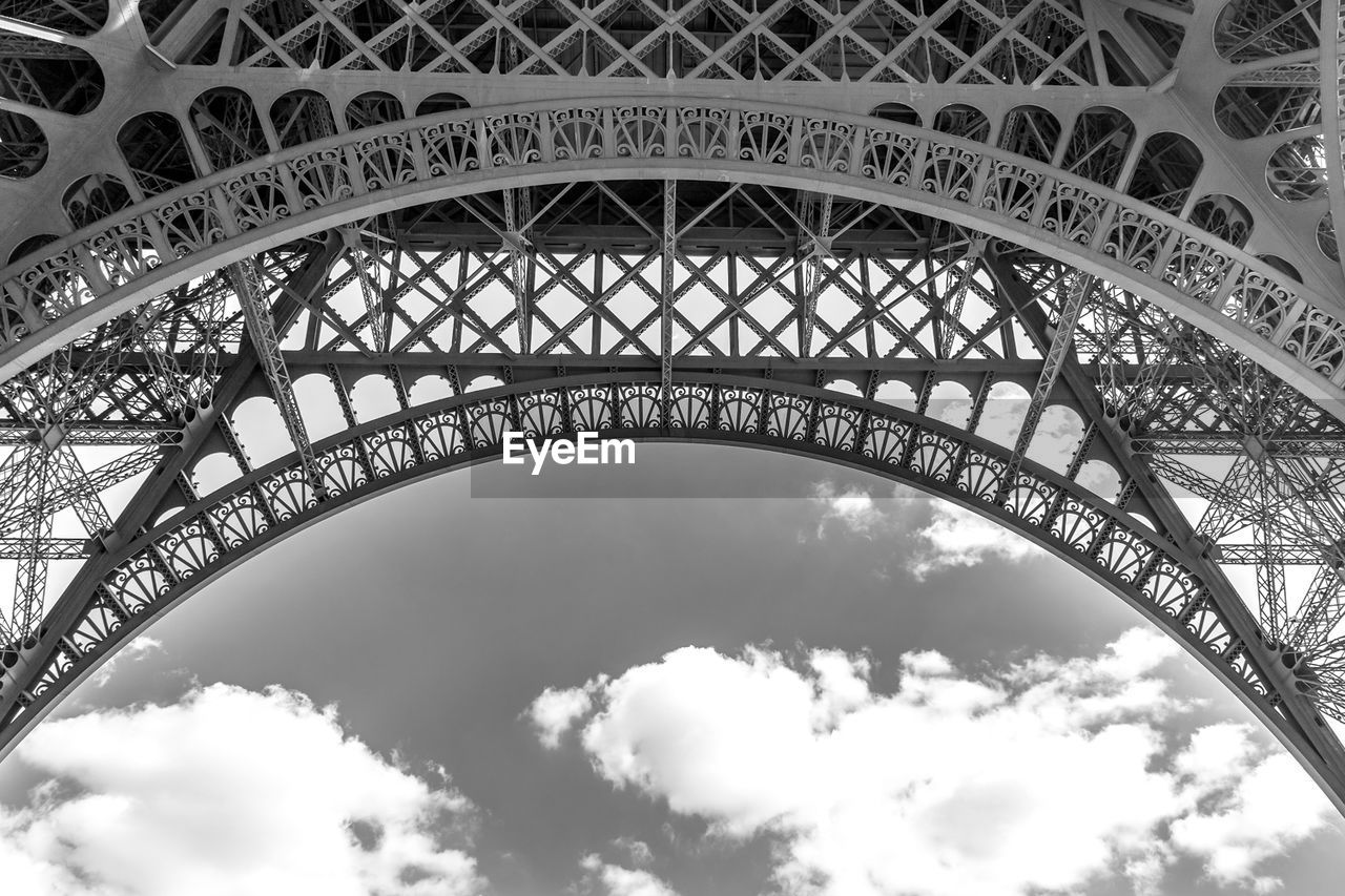 architecture, built structure, metal, low angle view, sky, cloud - sky, engineering, arch, travel destinations, city, architectural feature, tower, travel, nature, tourism, bridge, day, outdoors, iron, iron - metal, arch bridge, alloy, steel, directly below, architecture and art