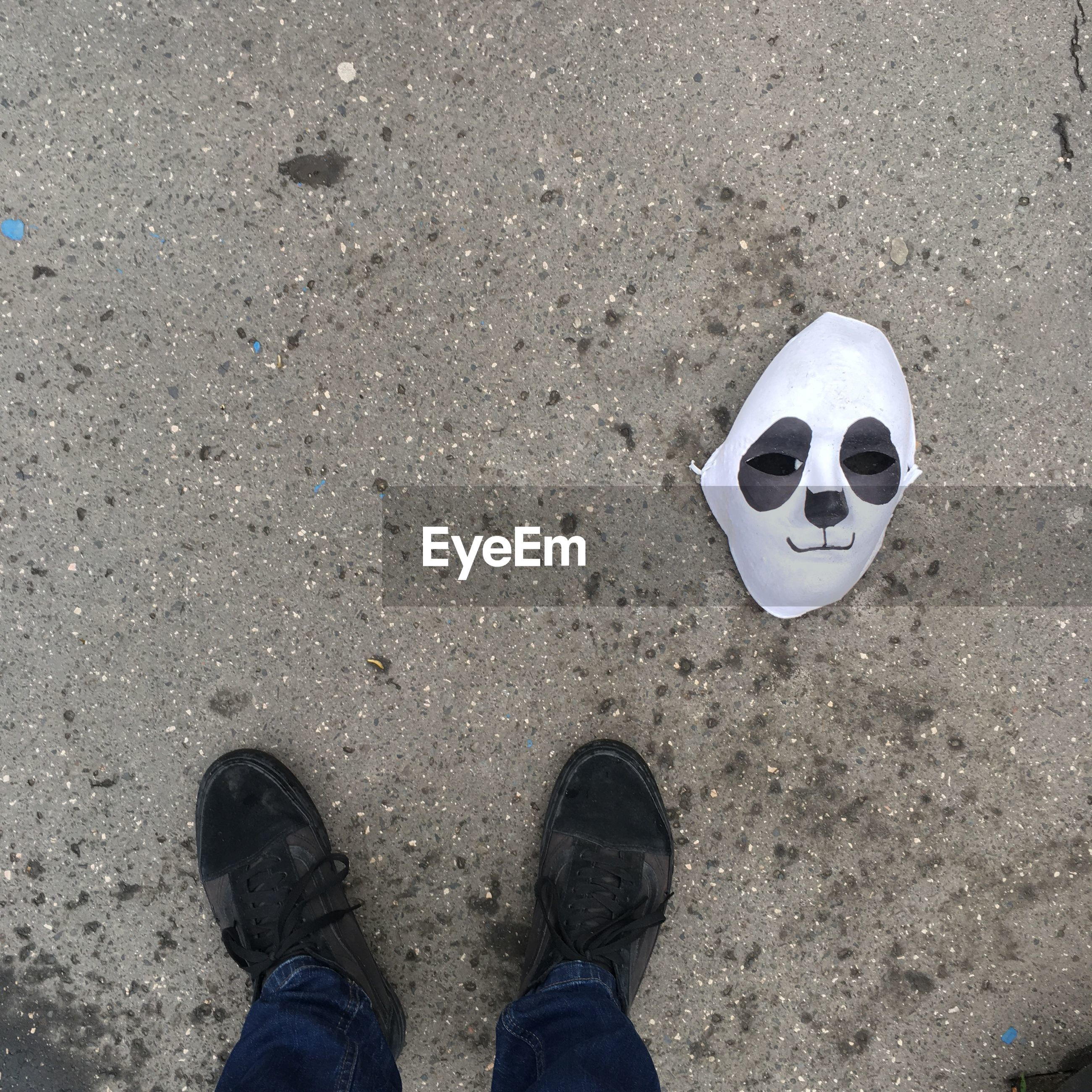 Low section of man standing by mask on road