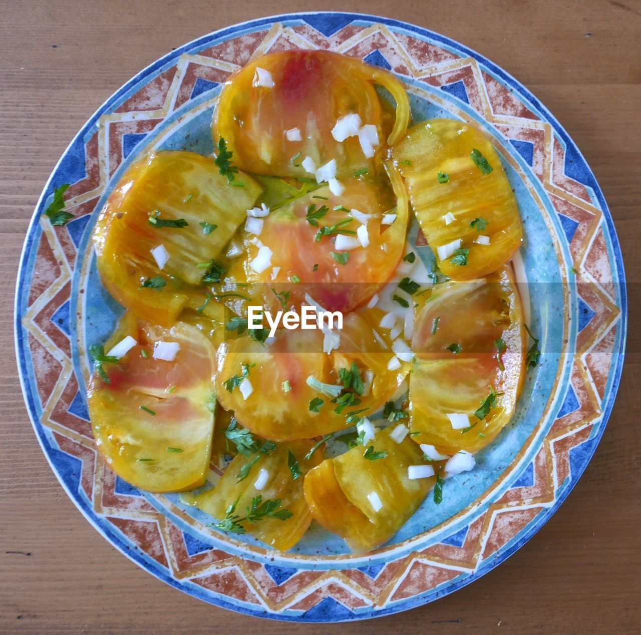 Tomato slices garnished with chopped onion served in plate