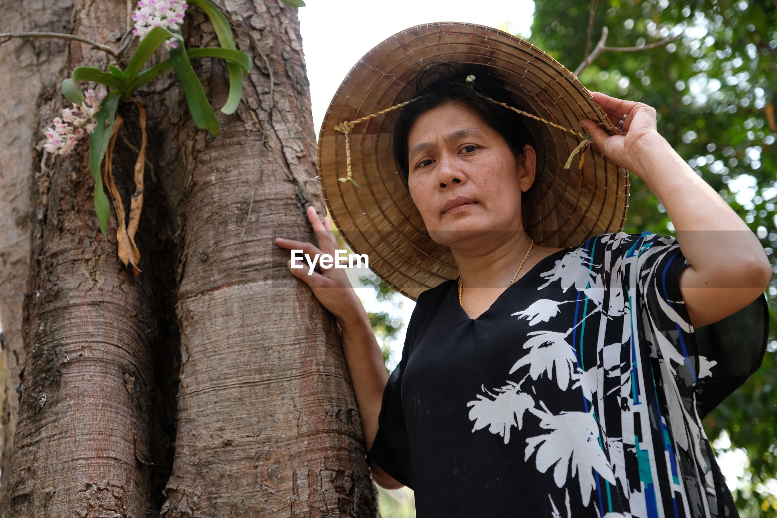 Portrait of mature woman wearing asian style conical hat by tree in forest