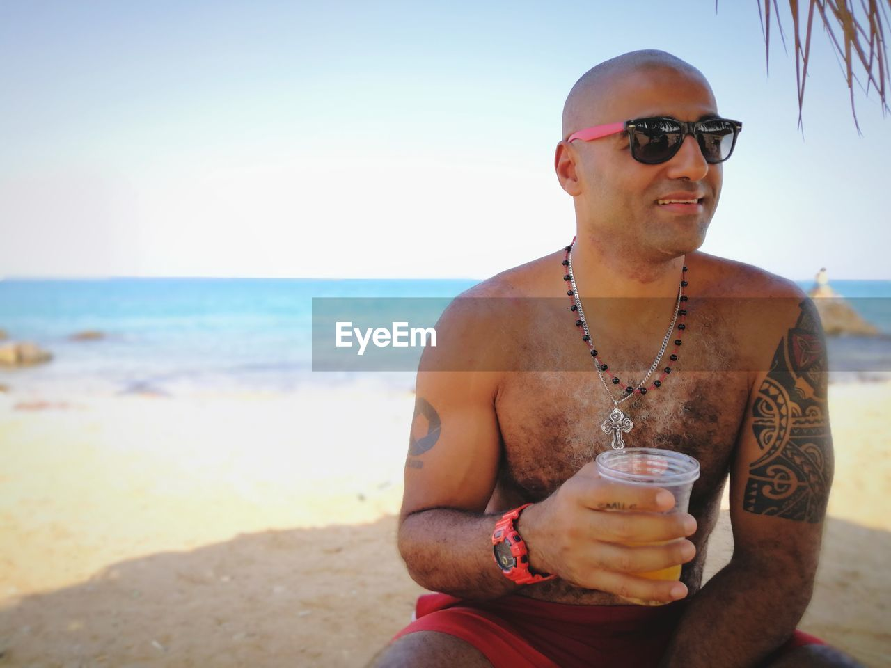 Smiling shirtless man sitting with drink at beach against sky
