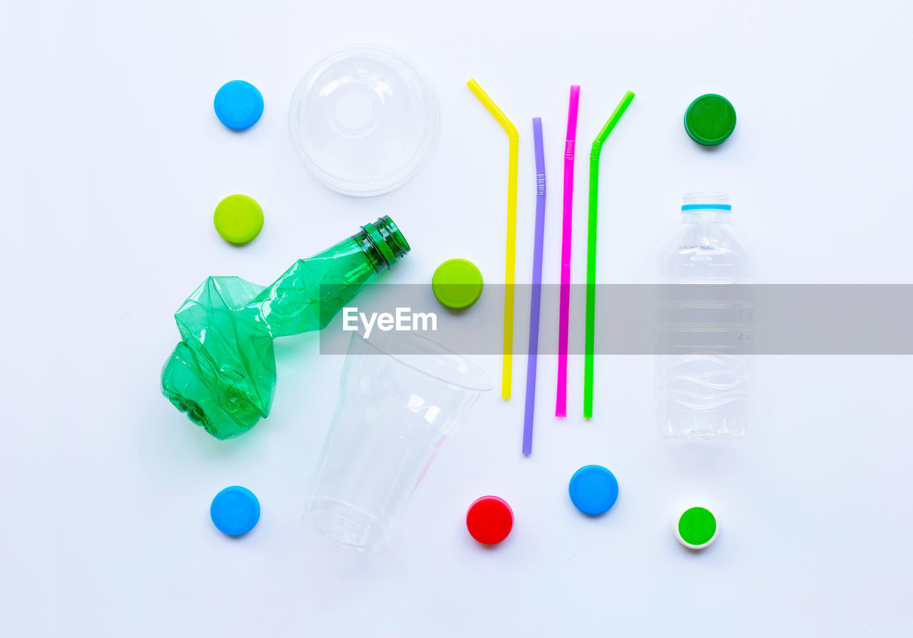 multi colored, still life, white background, indoors, green color, choice, studio shot, variation, no people, high angle view, large group of objects, close-up, plastic, blue, container, healthcare and medicine, directly above, thumbtack, bottle