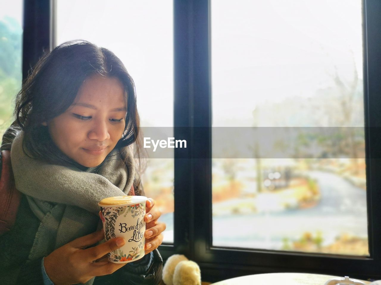 Woman holding coffee sitting by window in cafe